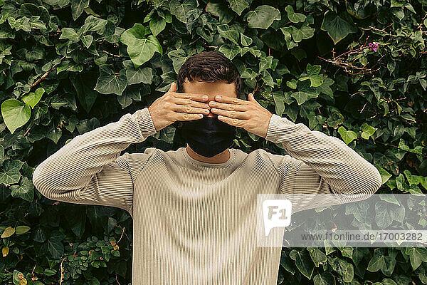 Junger Mann  der sich im Park während einer Pandemie die Augen mit den Händen vor Blättern verschließt Junger Mann, der sich im Park während einer Pandemie die Augen mit den Händen vor Blättern verschließt