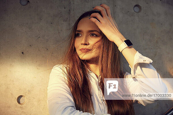 Businesswoman with hand in hair looking away while leaning on wall