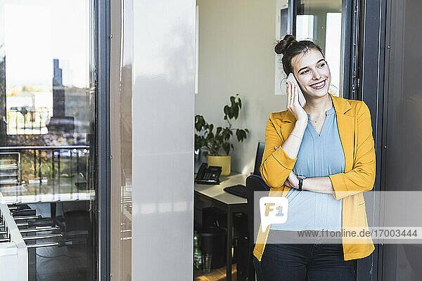 Geschäftsfrau  die mit einem Mobiltelefon spricht  während sie an der Tür im Büro steht Geschäftsfrau, die mit einem Mobiltelefon spricht, während sie an der Tür im Büro steht