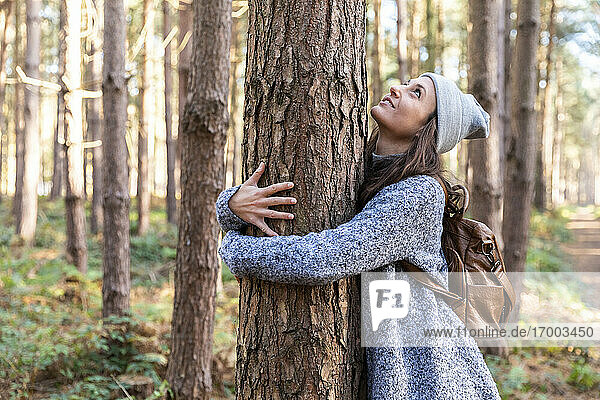 Female hiker embracing tree trunk while exploring in Cannock Chase woodland