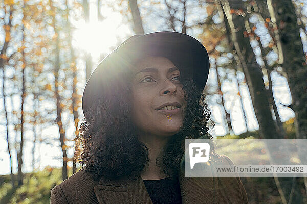 Curly hair woman wearing hat looking away while exploring forest