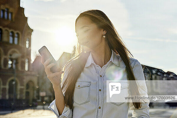 Businesswoman using mobile phone while standing against sky in city