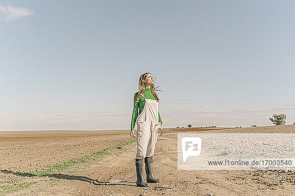 Young woman standing on dry field  with eyes closed