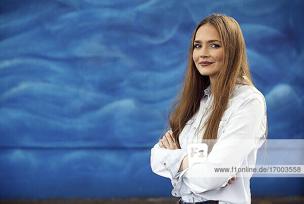 Businesswoman standing with arms crossed against blue wall