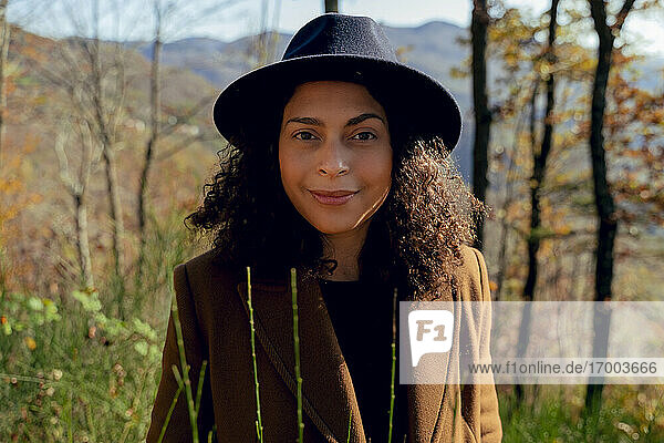 Beautiful female in hat smiling while standing in forest