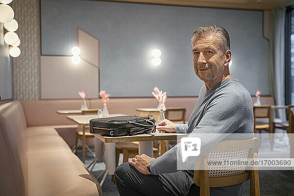 Smiling businessman with briefcase sitting at modern cafe