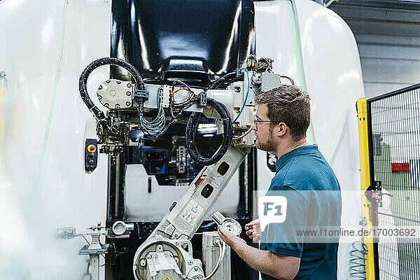 Männlicher Fabrikarbeiter hält ein Maschinenteil und prüft es im Stehen in der Industrie