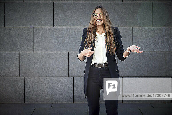 Happy businesswoman laughing while standing against brick wall