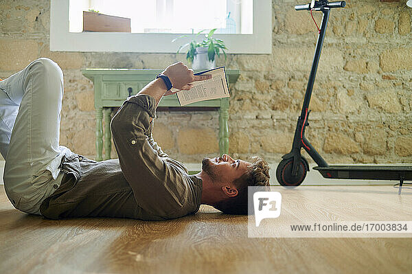 Caucasian man lying on floor while reading book in living room