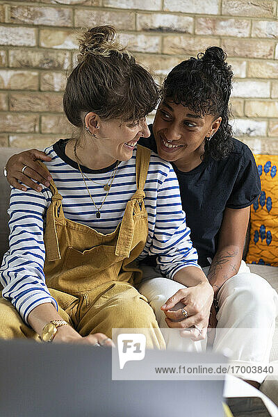 Smiling lesbian couple looking at each other while using laptop at home