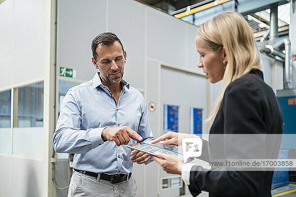 Unternehmerin und männlicher Kollege benutzen ein digitales Tablet  während sie in der Industrie stehen