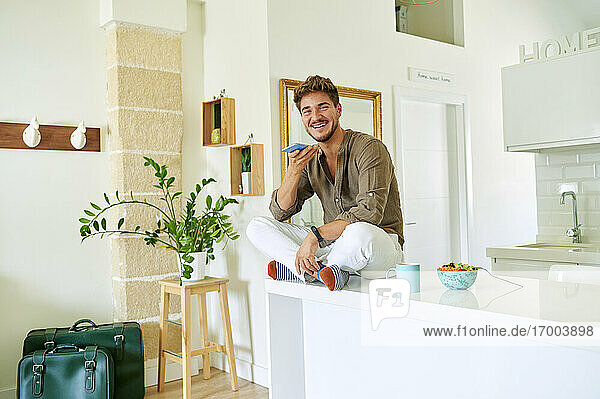Young man smiling while sending voicemail through smart phone in kitchen