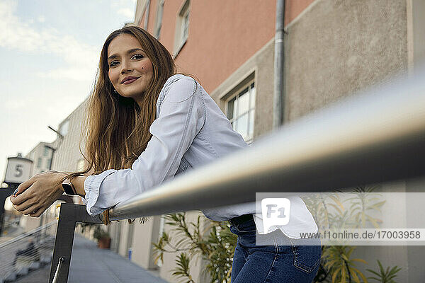 Businesswoman smiling while leaning on railing at balcony