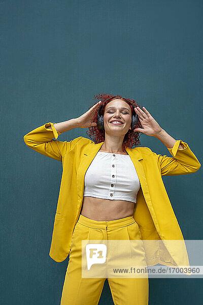 Junge Frau mit roten lockigen Haaren  die Kopfhörer trägt und Spaß beim Musikhören hat Junge Frau mit roten lockigen Haaren, die Kopfhörer trägt und Spaß beim Musikhören hat