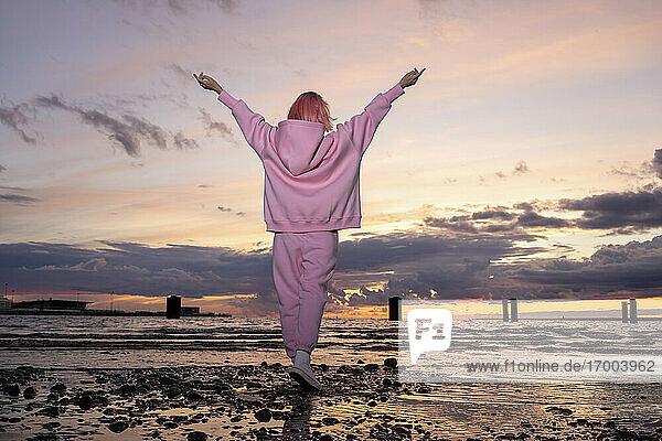 Rückansicht einer jungen Frau mit rosa Haaren und rosa Kapuzenshirt  die bei Sonnenuntergang am Strand steht Rückansicht einer jungen Frau mit rosa Haaren und rosa Kapuzenshirt, die bei Sonnenuntergang am Strand steht