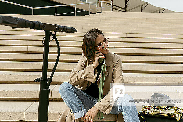 Lächelnde Frau  die mit einem Mobiltelefon spricht  während sie neben einem Saxophoninstrument und einem elektrischen Roller auf einer Treppe sitzt Lächelnde Frau, die mit einem Mobiltelefon spricht, während sie neben einem Saxophoninstrument und einem elektrischen Roller auf einer Treppe sitzt