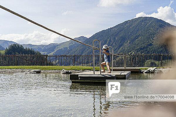 Kleines Mädchen überquert See auf kleinem Holzfloß