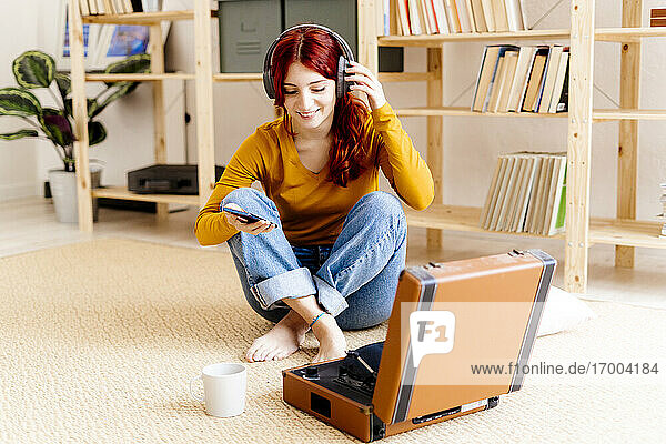 Smiling redhead woman wearing headphones using mobile phone while sitting by turntable at home