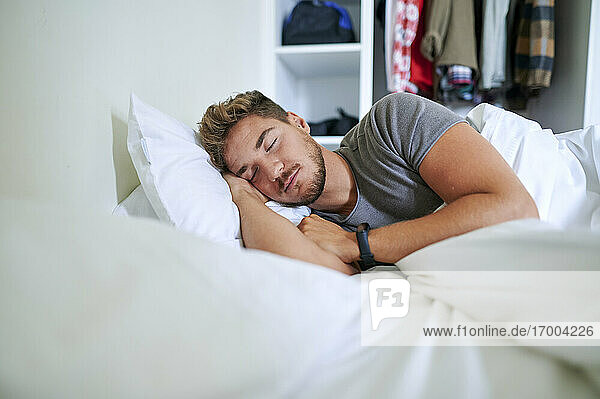 Young man fallen asleep on bed in bedroom at home