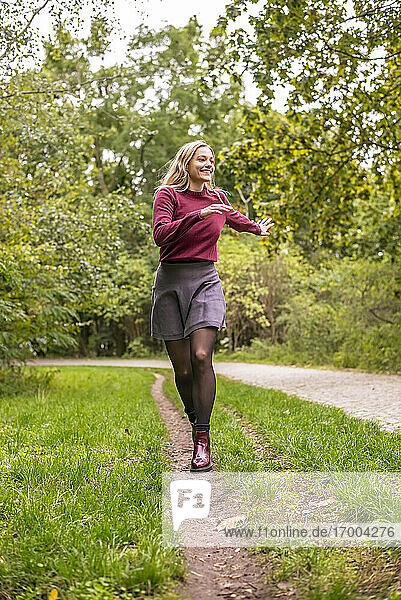 Cheerful woman running in park during autumn