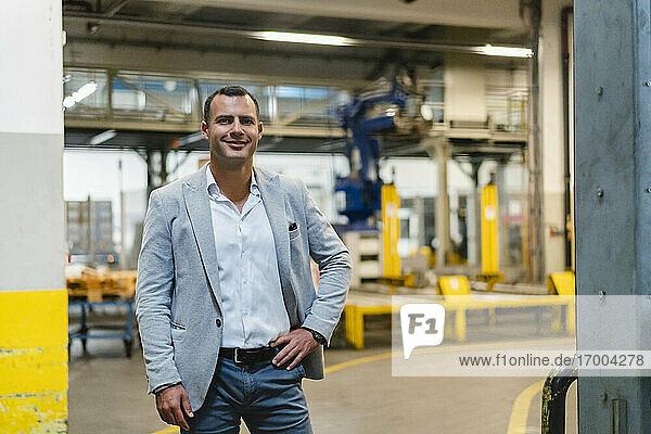 Lächelnder Geschäftsmann mit Hand in der Hüfte in einer Fabrik stehend