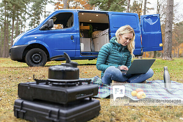 Woman working on laptop while sitting on picnic blanket at Cannock Chase