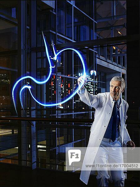 Mature male gastroenterologist examining esophagus in laboratory at hospital