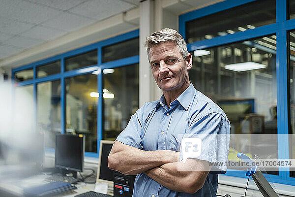 Älterer männlicher Unternehmer mit verschränkten Armen in einem Fabrikbüro