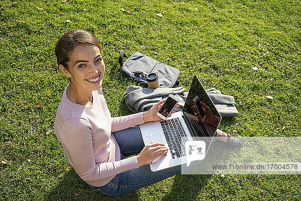 Lächelnde Geschäftsfrau  die im Herbst im Park im Gras sitzt Lächelnde Geschäftsfrau, die im Herbst im Park im Gras sitzt
