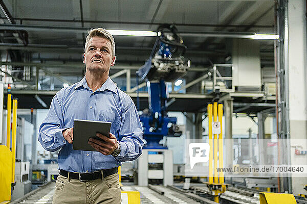 Mature supervisor holding digital tablet while looking away in industry
