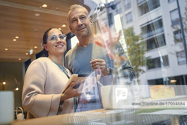 Confident business couple with digital tablet standing by window at modern cafe