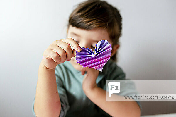 Girl holding handmade heart with origami against wall at home