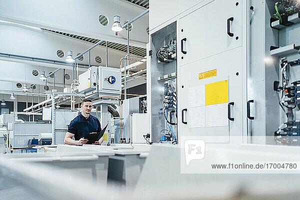 Männlicher Techniker mit Aktenordner umgeben von Maschinen in einer Fabrik
