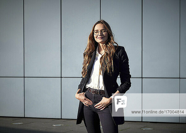 Smiling businesswoman standing with hands in pockets against wall