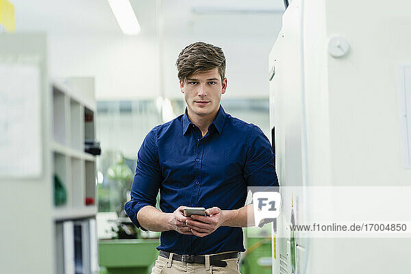 Confident businessman holding mobile phone while standing in factory