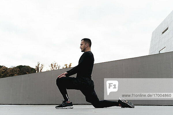Man looking away while doing lunge exercise outdoors