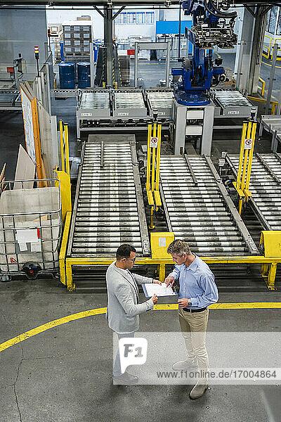 Geschäftsmann und Manager diskutieren über ein Dokument  während sie sich in einer Fabrik treffen