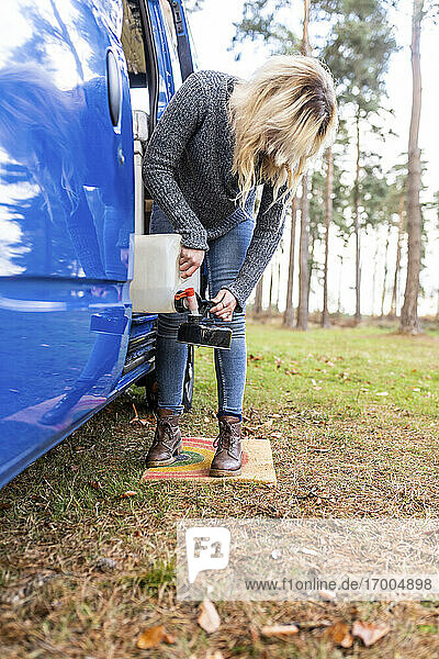 Blond woman filling water in camping teapot at Cannock Chase