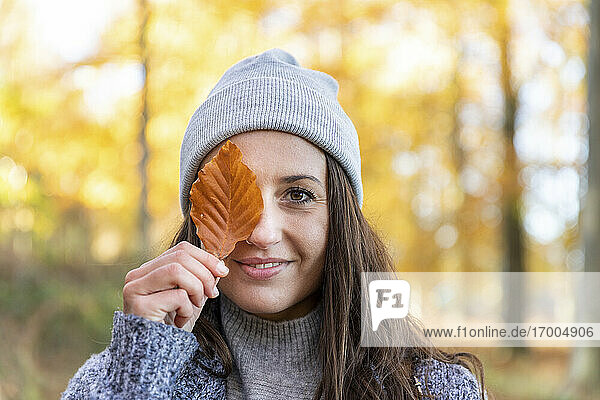Beautiful woman covering eye with autumn leaf in Cannock Chase woodland