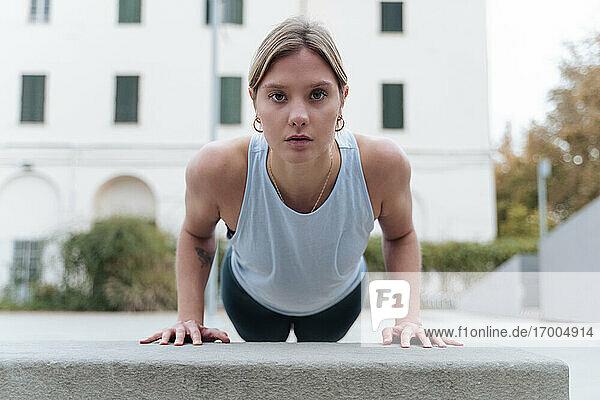 Young woman doing push-ups outdoors