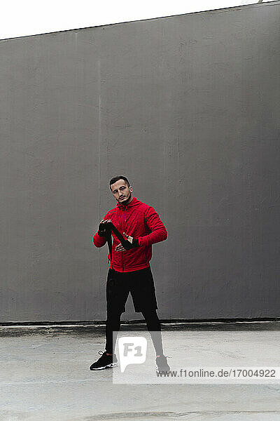 Male athlete tying boxing wrap in hand while standing against wall