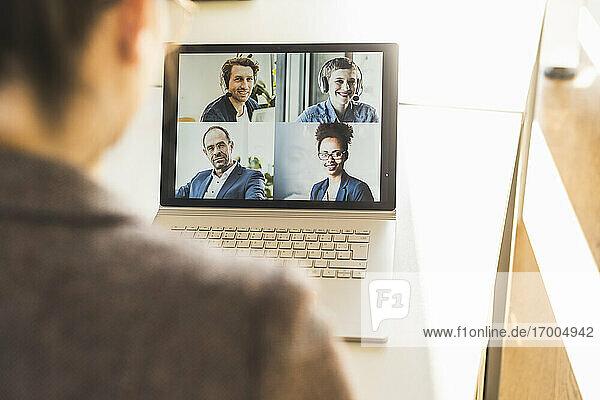 Geschäftsfrau  die an einer Videokonferenz auf einem Laptop im Büro teilnimmt Geschäftsfrau, die an einer Videokonferenz auf einem Laptop im Büro teilnimmt