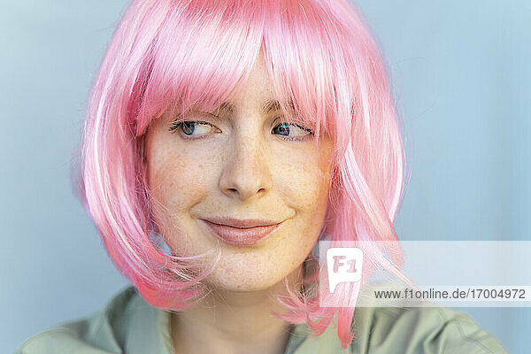 Portrait of young woman wearing pink wig glancing sideways