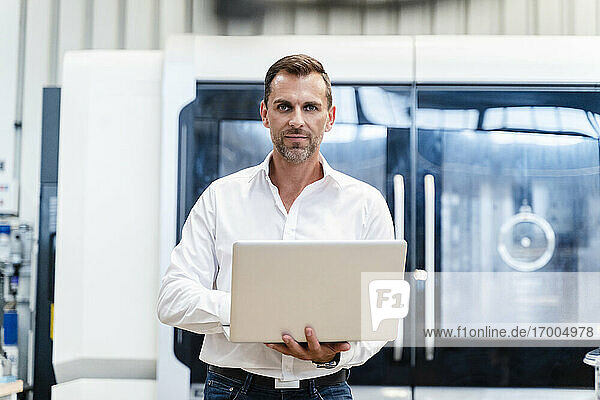 Confident businessman holding laptop while standing in industry