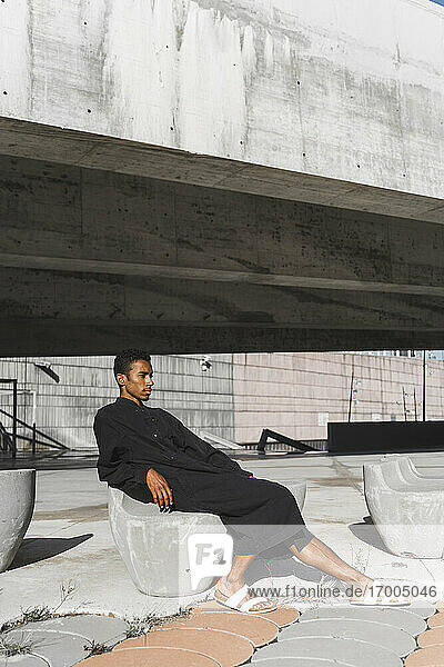 Young man wearing black kaftan relaxing on concrete stucture outdoors