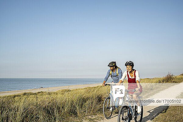 Smiling woman wearing cycling helmet riding bicycle with man against clear sky