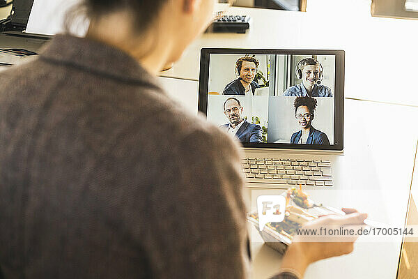Businesswoman having lunch while attending video conference through laptop at office