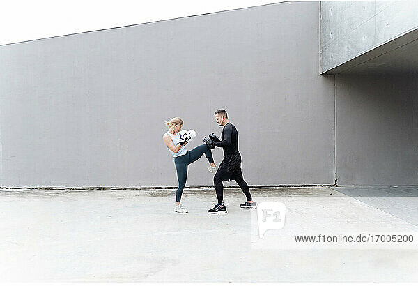 Woman practicing kickboxing with man while standing against wall