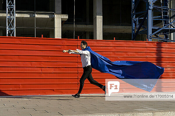 Businessman wearing superhero cape running on pavement