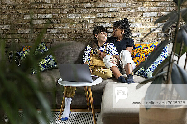 Young lesbian couple looking at each other while sitting on sofa at home